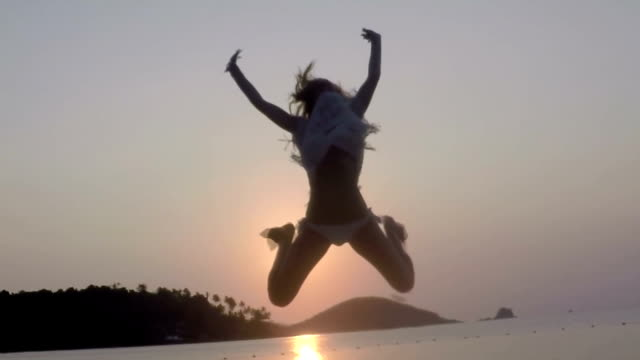 Young woman jumping in slow motion on the beach at sunset