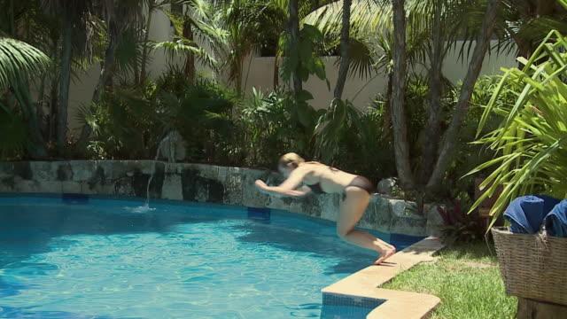 SLO MO, WS, Young woman jumping into swimming pool, Playa del Carmen, Quintanaroo, Mexico