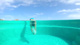 SLOW MOTION: Young woman jumping into the resort swimming pool