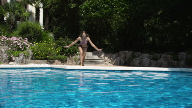 young woman jumping into water in pool - bikini stock videos and b-roll footage
