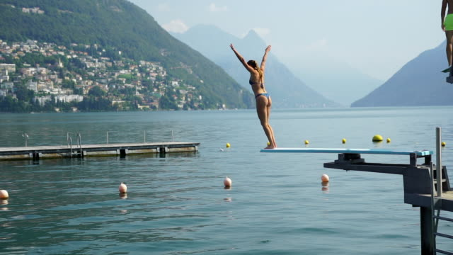 young woman jumping off diving board into lake - switzerland stock videos & royalty-free footage