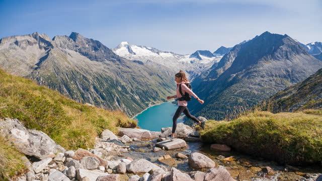 vídeos de stock, filmes e b-roll de jovem pulando sobre corrente de montanha em paisagem majestosa - cruzar