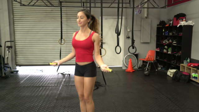 ws young woman jumping rope in a gym. - gymnastic rings stock videos & royalty-free footage