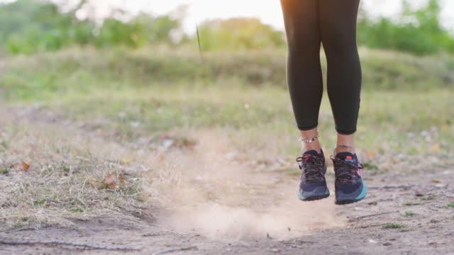 vídeos de stock e filmes b-roll de young woman jumping rope in nature - corda