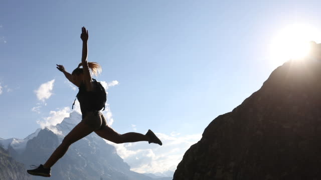 young woman jumps from rock ridge above mountains - ponytail stock videos & royalty-free footage