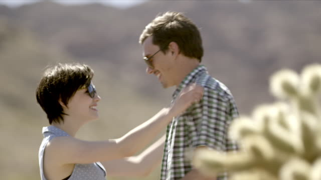 young woman jumps into boyfriend's arms, spins, and kisses him in cactus grove - cute cactus stock videos & royalty-free footage