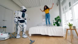 Young woman jumps on bed while a robot cleans floor.