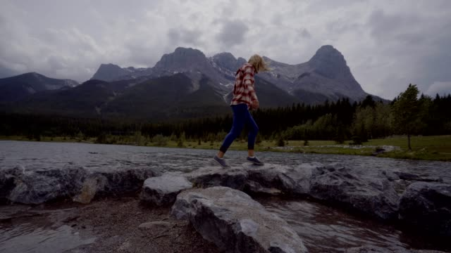 junge frau springt fels zu fels am bergsee - stein stock-videos und b-roll-filmmaterial
