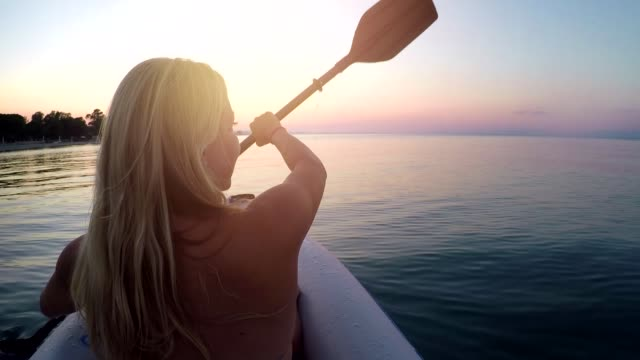 young woman kayaking on aegean sea at sunset - pagaiare video stock e b–roll