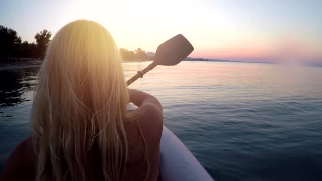 young woman kayaking on aegean sea at sunset - andare in canoa video stock e b–roll