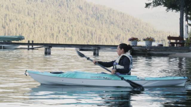 若い女性の穏やかな湖でカヤック - カヤック点の映像素材/bロール