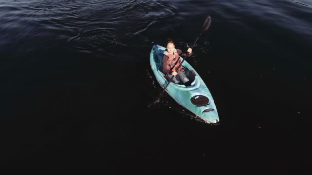 4K AERIAL: Young woman kayaking