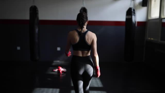 junge frau kick boxer zu fuß in richtung der boxsack - legging stock-videos und b-roll-filmmaterial