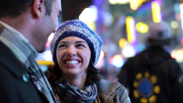 Young woman kisses boyfriend on cheek and laughs beneath the lights of Times Square