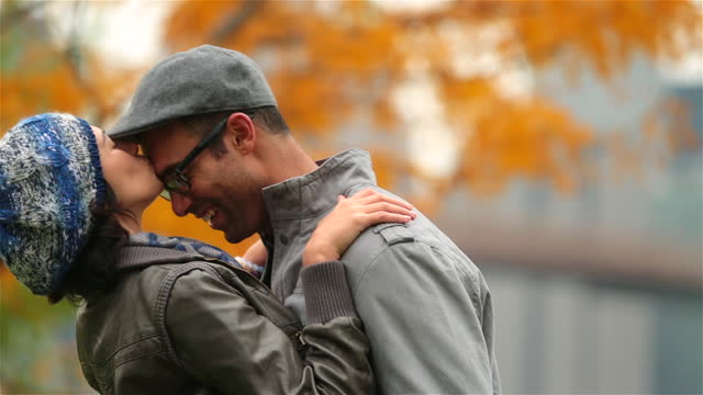 young woman kisses boyfriend's forehead as he pulls her in close in autumn park - forehead stock videos and b-roll footage