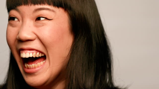 Young woman laughing against white background