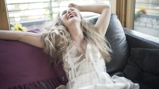 vídeos de stock, filmes e b-roll de a young woman laughing and smiling on a sofa. - roupa formal