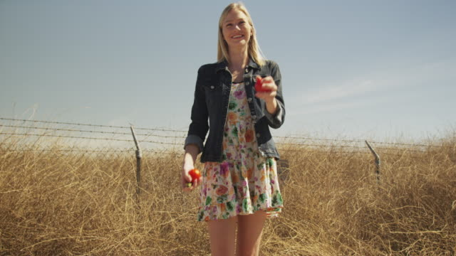 vídeos de stock, filmes e b-roll de young woman laughing and throwing tomatoes - human fertility