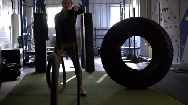young woman laughing as she uses battle ropes for the first time - människoarm bildbanksvideor och videomaterial från bakom kulisserna