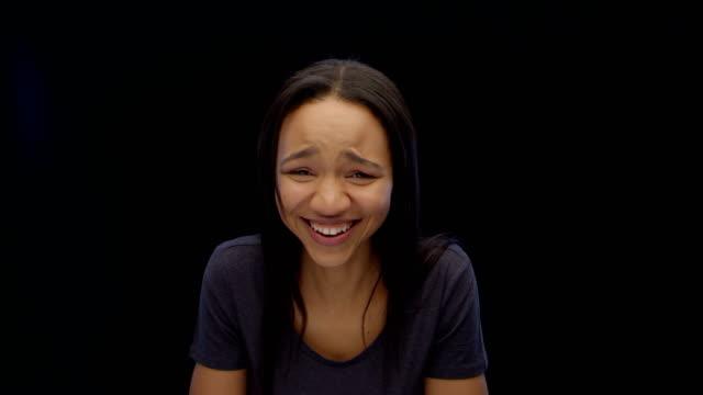 Jeune femme rire en regardant un objet imaginaire, drôle