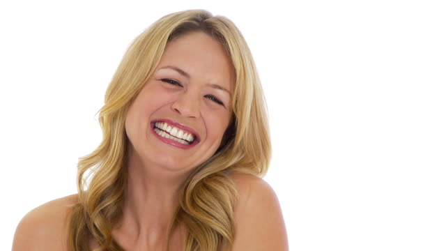 Young woman laughing on white background