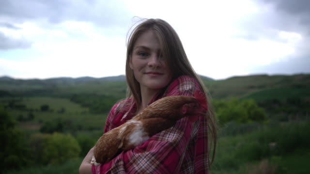 cu young woman laughing while holding a chicken - teenagers only stock videos and b-roll footage