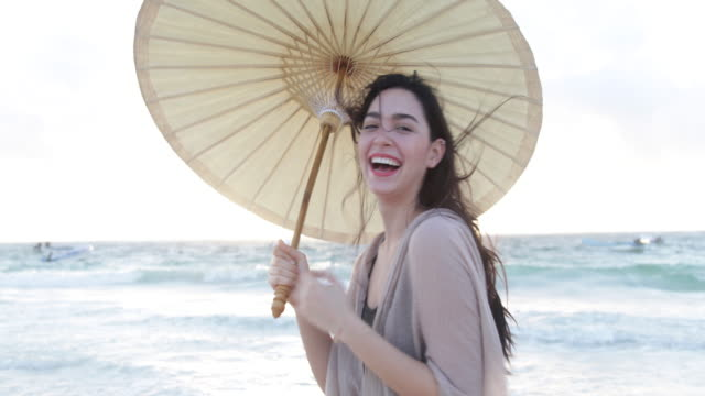 young woman laughing,holding parasol on windy beach. - rufsig bildbanksvideor och videomaterial från bakom kulisserna