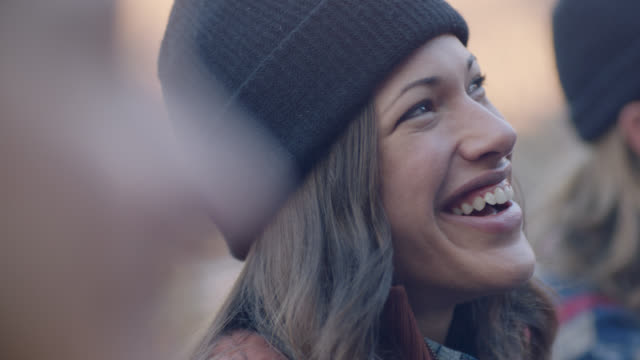 stockvideo's en b-roll-footage met cu. young woman laughs and talks with friends on camping trip. - milleniumgeneratie