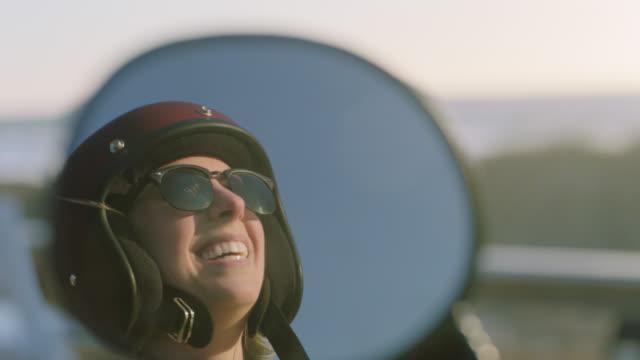 vídeos de stock, filmes e b-roll de cu slo mo. young woman laughs reflected in motorcycle side mirror. - capacete esportivo