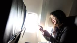 Young woman laughs while using smartphone during flight