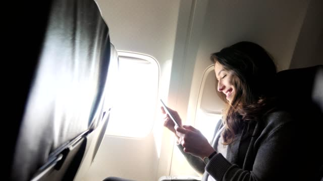 young woman laughs while using smartphone during flight - abitacolo video stock e b–roll