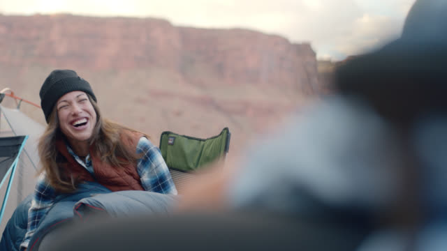 Young woman laughs with friends on Moab camping trip.