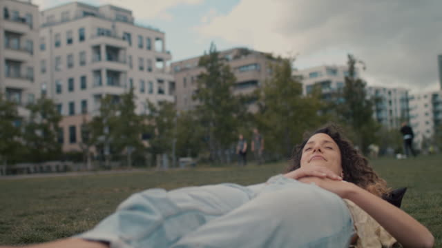 young woman laying down in park in central berlin - ruhen stock-videos und b-roll-filmmaterial