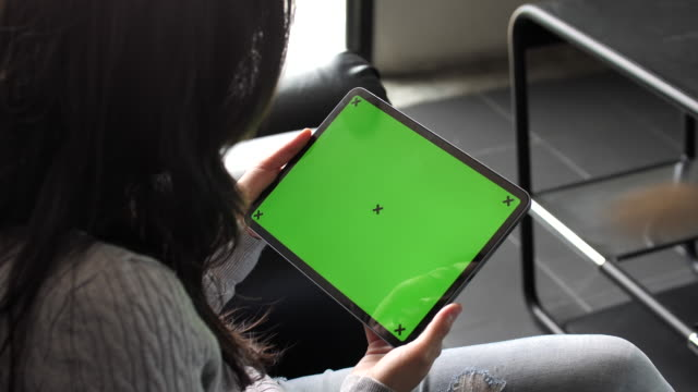young woman laying on the sofa looking at digital tablet with green screen, horizontal - using digital tablet stock videos & royalty-free footage