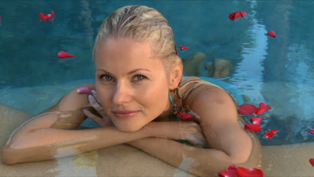 cu young woman leading at edge of pool / cape town, south africa  - solo una donna di età media video stock e b–roll