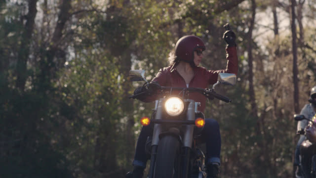 stockvideo's en b-roll-footage met slo mo. young woman leading friends on motorcycles uses hand signals to communicate on wooded highway drive. - motor