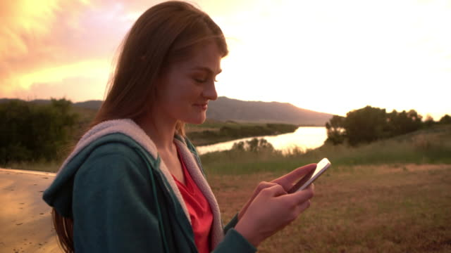 cu young woman leaning against her truck looking at her phone - one teenage girl only stock videos & royalty-free footage