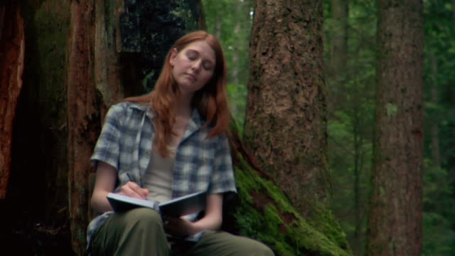 young woman leaning against moss-covered tree and writing in journal - kelly mason videos 個影片檔及 b 捲影像