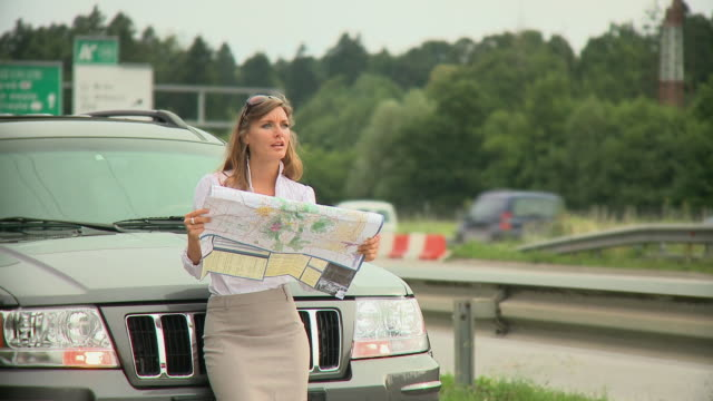 ms young woman leaning on car hood and looking at road map next to highway, ljubljana, slovenia - road map stock videos & royalty-free footage