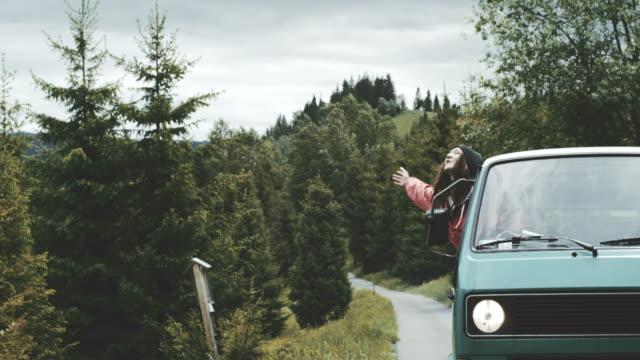 vídeos de stock, filmes e b-roll de jovem mulher, inclinando-se fora da janela da van e acenando. - vintage car