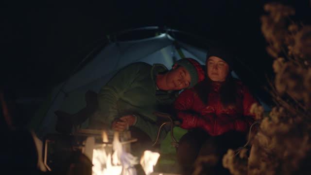 vidéos et rushes de young woman leans head on friend as they sit by the campfire. - tente