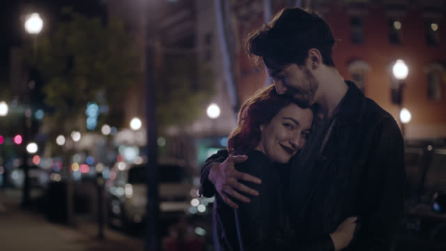 ms slo mo. young woman leans on boyfriend and smiles at camera as he puts his arm around her on city street corner. - generazione y video stock e b–roll