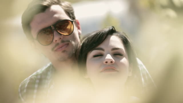 young woman leans on boyfriend as he kisses her in cactus grove - hot kiss stock-videos und b-roll-filmmaterial