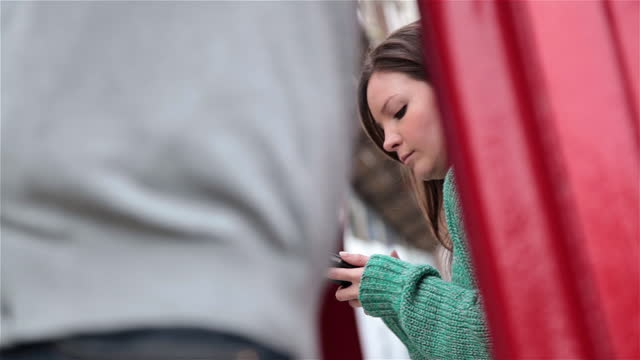 young woman leans on red telephone booth and texts on smartphone. - emozione negativa video stock e b–roll