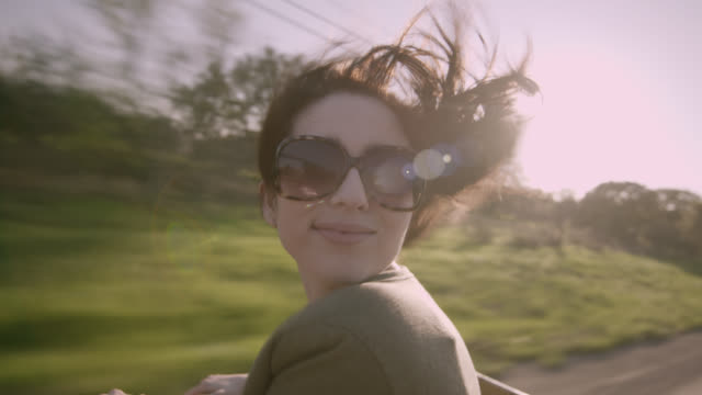 Young woman leans out the back of classic convertible and smiles as her hair blows in the wind