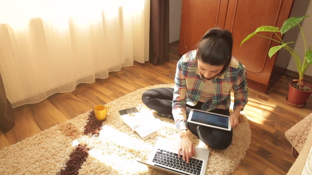 young woman learning at home. - cross legged stock videos & royalty-free footage