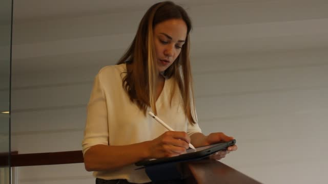 young woman librarian writing on her tablet - bibliotecario video stock e b–roll