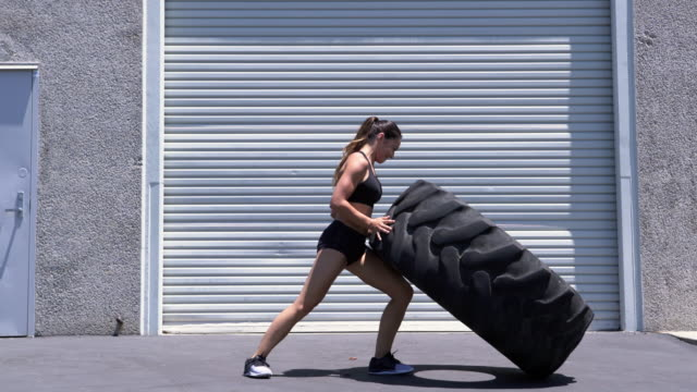 WS Young woman lifting a giant tire