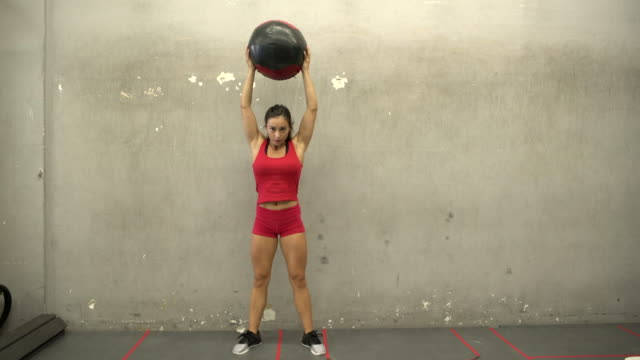WS Young woman lifting a medicine ball in a gym