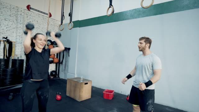 vídeos de stock, filmes e b-roll de jovem mulher levantando halteres com um personal trainer na academia de ginástica - instrutor de fitness